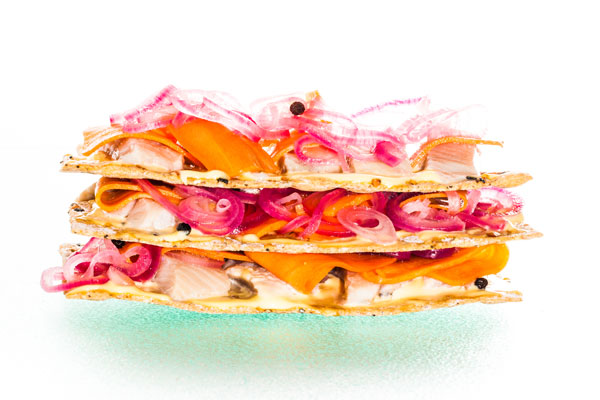 Pickled herring, pickled red onions and carrots on rye crisp bread