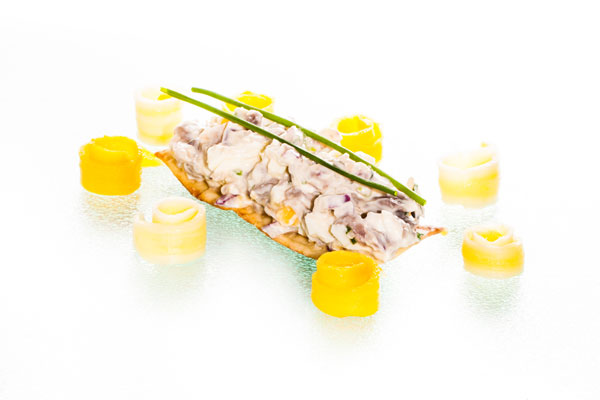 Pickled herring salad with eggs and chives on crisp bread