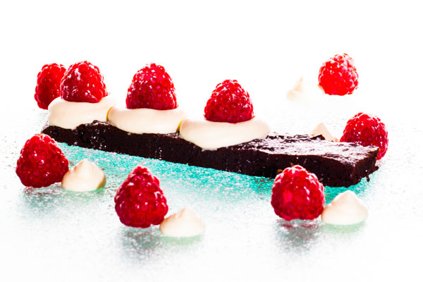 Chewy chocolate cake with fresh raspberries and whipped cream