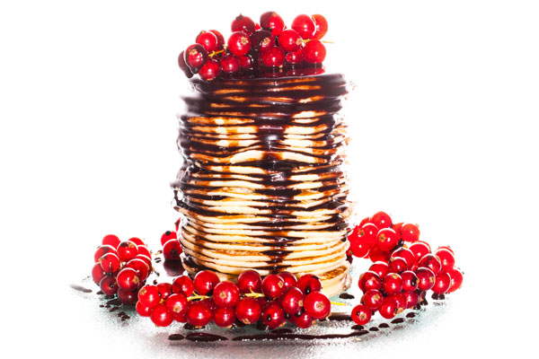 Mini pancakes with chocolate sauce and red currants